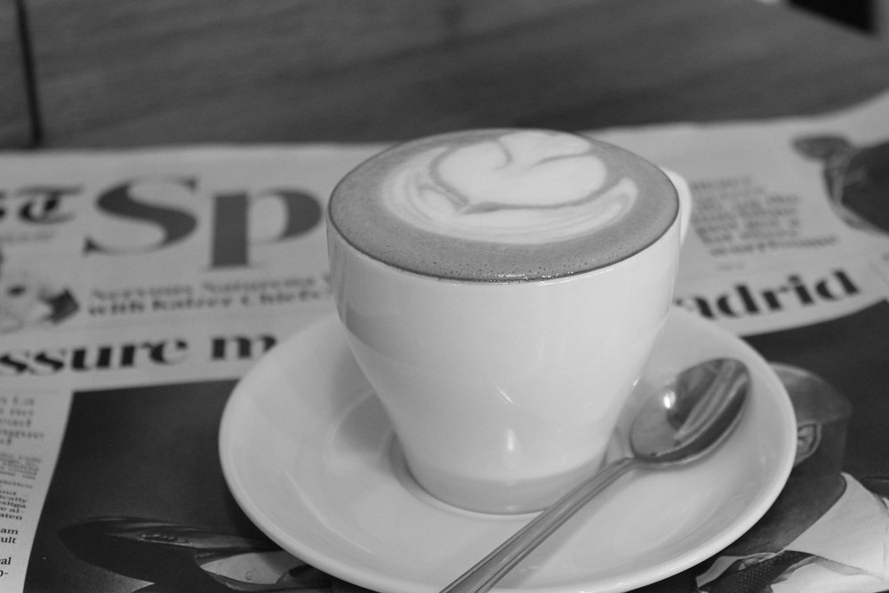 A macchiato with latte art sits atop a newspaper on a table