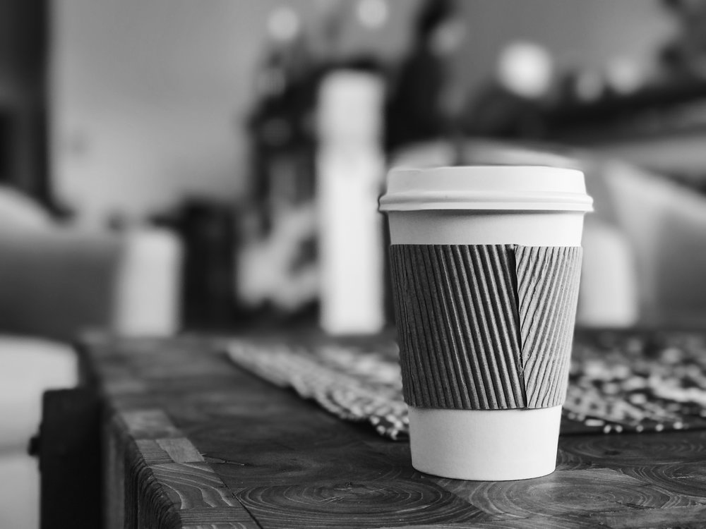 A disposable single-use coffee cup sits on a table.