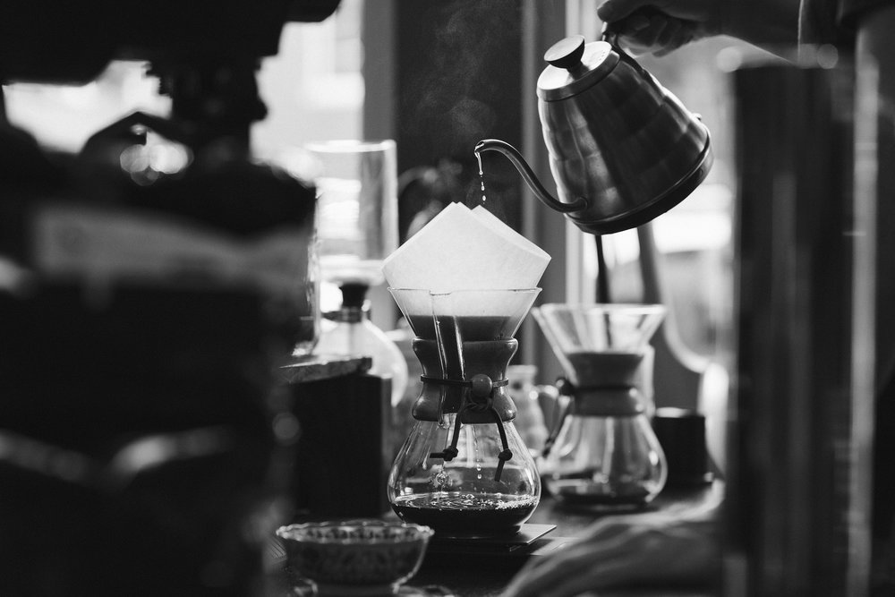 A barista pours hot water over grounds in a Chemex coffemaker in a cafe