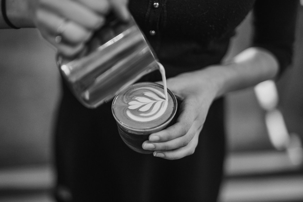 A barista pours a latte, seen from above.