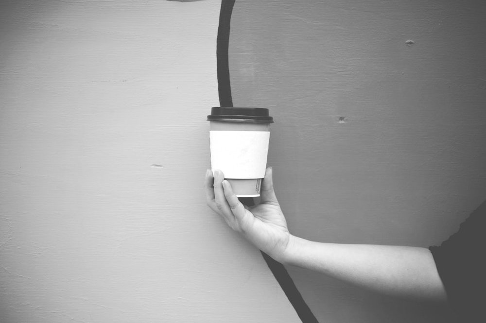 A takeaway coffee cup is held in front of a painted wall