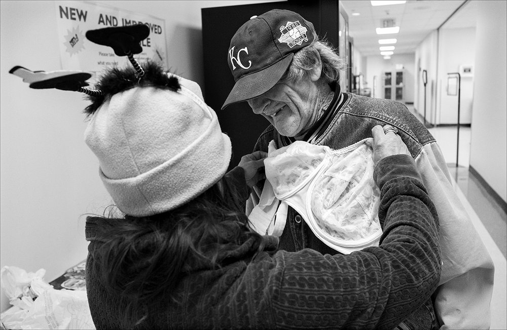 "February 2017:  Holding a bra up to Clarence's shirt, Vickie jokes with Clarence, calling him an ""old goat,"" as the two look through items on the ""free table"" at the Quincy Senior and Family Resource Center. At times, the couple collects aluminum cans, even cashing them out for less than a $3 payday, to help pay for necessities when they run out of money before the end of the month."