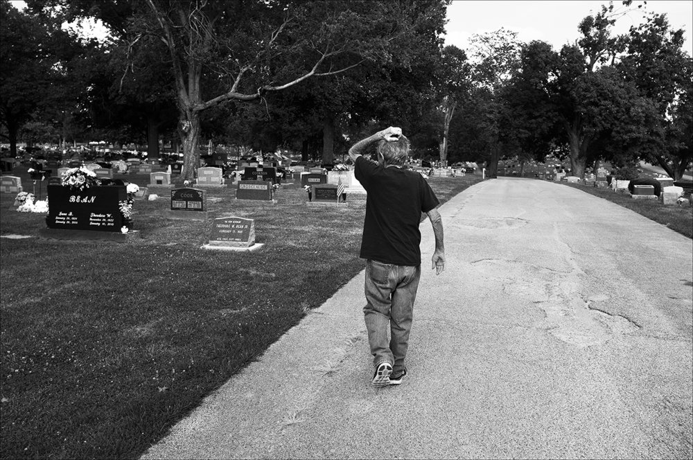 "July 2017:  Clarence searches for Vickie's burial plot in Green Mount Cemetery in Quincy. He's heard Vickie's remains may have been placed next to her parents' grave, but thus far he's been unable to find her. ""Clarence just sits on the front porch mostly. He cries every day, missing Vickie,"" Brenda says of Clarence, who was very active before her death."