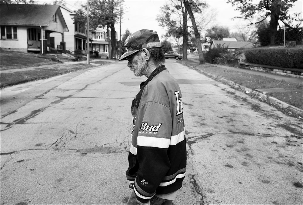 "November 2017:  Visibly thinner two months after his diagnosis of lung cancer, Dennis walks home from a doctor's appointment. He weighed 145 pounds in September and now weighs 110 pounds. Dennis says the demolition work he's done for years probably contributed to the cancer. ""They do things illegal all the time."" Now Dennis has stopped working his demolition job, and says he's too weak to walk Levi. ""I've had no food for two days. I'm in pain. I can't deal with this pain anymore today."""