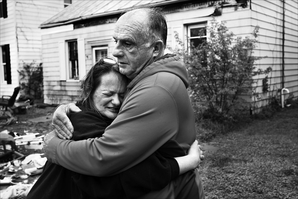 """April 2017:  Elizabeth breaks down in tears as one of several volunteers with trucks arrive to help her after learning of her plight on social media. """"I was cold. I was really tired. It was 1 in the morning. My son had come over for a little while and had put some very heavy things on the U-Haul. How can you be organized when they take everything out of your house, when you're not there when they do it?And then nothing is packed in boxes except for the few I had packed? They're just thrown in a pile. My clothes are all wet. My clean work clothes of seven white shirts and about six pairs of white pants and three aprons are all soaked. Loading that U-Haul, I'm 55. I really don't have aches and pains but I was pretty damn tired lifting all those heavy boxes. I was there all night long,"""" Elizabeth said."""