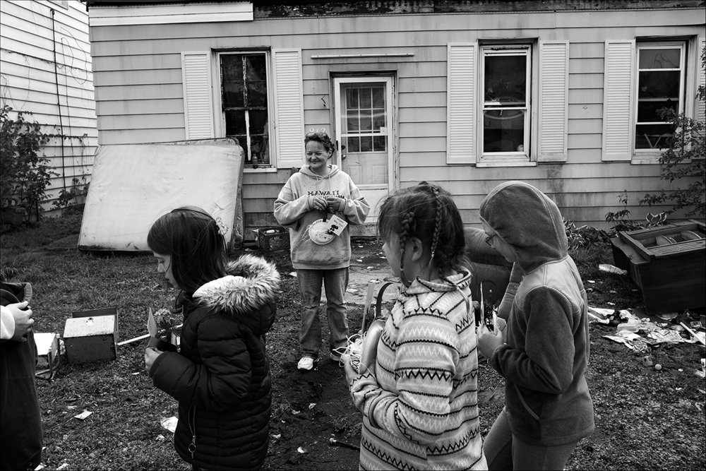 May 2017:  Three days after being evicted from her home of 20 years, Berrian Elementary School third-grade students deliver May Day flowers to Elizabeth, as they have for years throughout the neighborhood. She takes a short break from gathering her belongings to bask in the memory of receiving this special blessing from the children all these years knowing this will be the last time.