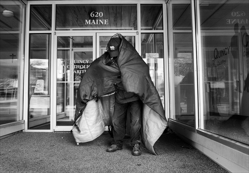 "April 2017:  James awakens in front of Catholic Charities on Maine Street and wraps himself in his sleeping bag to stave off the morning chill.  ""I prefer hot weather over cold. I'll soak a T-shirt in water and put that on at night. I'll sleep like a baby.""  James will gather up his things quickly to avoid being approached by police."