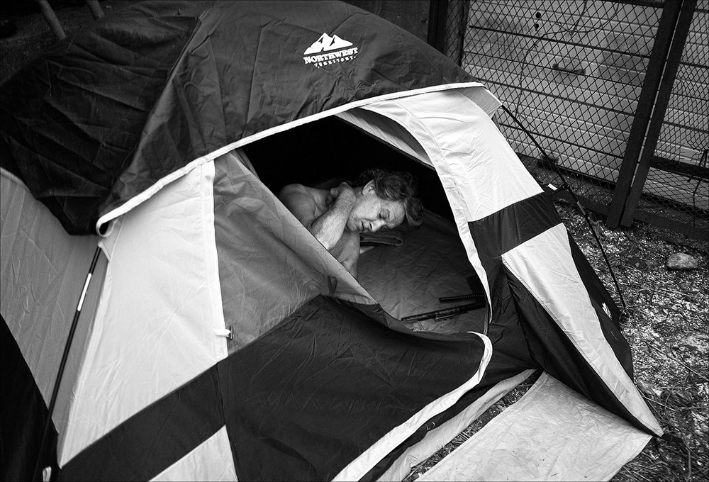 "May 2017:  Hidden on a small brushy piece of land in the District, James wakes from a restless night.  ""My joints and muscles used to be strong, but now I ache all the time.""  His tent was later stolen when he had to abandon it for a week after suffering a serious leg injury.  His tent and belongings, including his Bible, are gone."