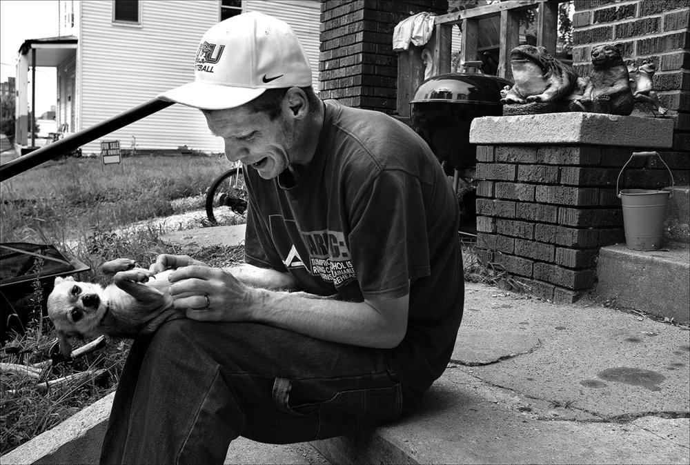 """August 2016:  During a break from making rounds to the food pantries in town, James takes a moment to play with a friend's dog. James says he likes to write poems, but then his depression kicks in and his whole mood changes. """"My mood goes from upbeat to down low, almost suicidal thoughts,"""" he says."""