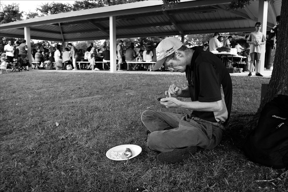 """August 2016:  After walking 26 blocks in the August heat to attend church, James sits by himself at a church picnic following services. The meal is the only source of food he will have that day.  """"The friends I had would let me stay until my food stamps or my SSI check kicked in. I'd help pay the rent and help put food in the house and the next day, within a day or two, they'd kick me out because they got what they wanted. They figured I'd be the perfect person for that, because I'm living on the street. It just brings my self-esteem back down to where it was, back down real low. Sometimes it just makes me feel like I'm a welcome mat everybody walks on to get what they want and then when I actually need help, there's nobody there to turn to."""""""