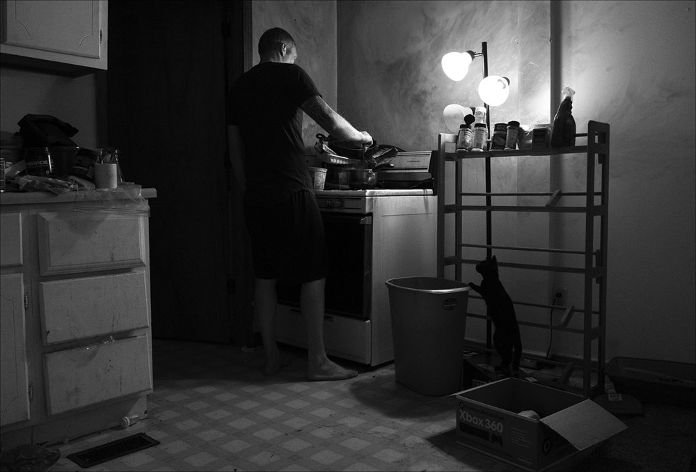 "July 2017:  With window blinds drawn against the sunlight outside, Sean makes himself a meal from a can of soup.  ""I watched, just like everybody else, my world fall apart. I came back, wife was already pregnant by somebody else that she had moved into my house. I had such animosity. Like, I was tired of the world. I was tired of the world turning it's back on me so I turned my back on the world and I became a hateful, cruel person.  Over there I had a purpose. I enjoyed protecting people. I wanted to make sure everybody came home, even if that meant giving my life. Being a homeless veteran was the easiest thing to walk into.""  Sean says seeing the goodness in other homeless people helped him. ""Seeing that good in them -  It's enough to keep you from killing yourself.  These people who have given me a home off the streets - they remind me of me before, before I deployed. Just somebody who'd just give you the shirt off their back, you know. They don't owe you nothing. They just did it cuz. And that reminds me a lot of how I used to be. How I want to be once again. Someone who cares for others when nobody else will."""