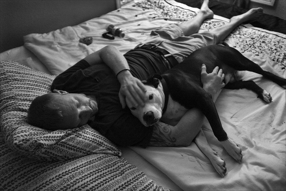 "August 2017:   Sean, 28, rests with his dog, Zeus, where he shares an apartment with a couple living in poverty, who took him in.  Sean found the dog in a dope house where he says Zeus was being beaten.  An untrained companion dog, Sean says Zeus can detect when he's about to have a blackout.  ""Blacking out is the worst. It can happen anywhere. It's almost like I can watch but I have no control over what I'm doing. It's like a sudden aggressive, mean, hateful personality that can arise if someone yells at you, for no reason or something like that. One little nip to my leg to get my attention - it's his way of saying, stop. He's pulled me out of situations that could have been detrimental to me and others.""   Sean says his dog means everything to him. ""Like when you feel there's no purpose for you on this planet anymore, that will eat your soul alive. That would be the reason you commit suicide. When you don't feel like you'd do anybody any good. If it wasn't for my dog, I would have pulled the plug a long time ago, but I couldn't do that to him, he's always been there for me. Despite how cruel you can be, he's gonna love you with all his heart, and that's the bit of hope I need. Zeus is a loving dog. He has love in his soul. Even when things are crappy and you're sleeping on the streets, he gonna sleep right next to you, and he's not miserable. He's just happy you're there with him."""