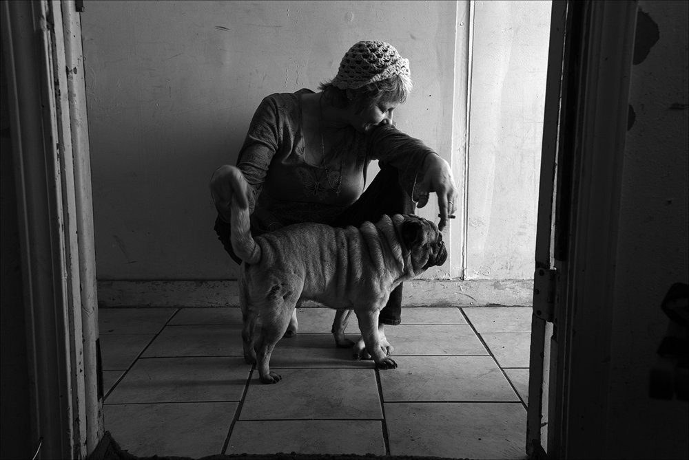 February 2017:  Trish sits with her dog in the apartment she lived in before being evicted. By spring she will be homeless, living in abandoned buildings, while trying to find a job.
