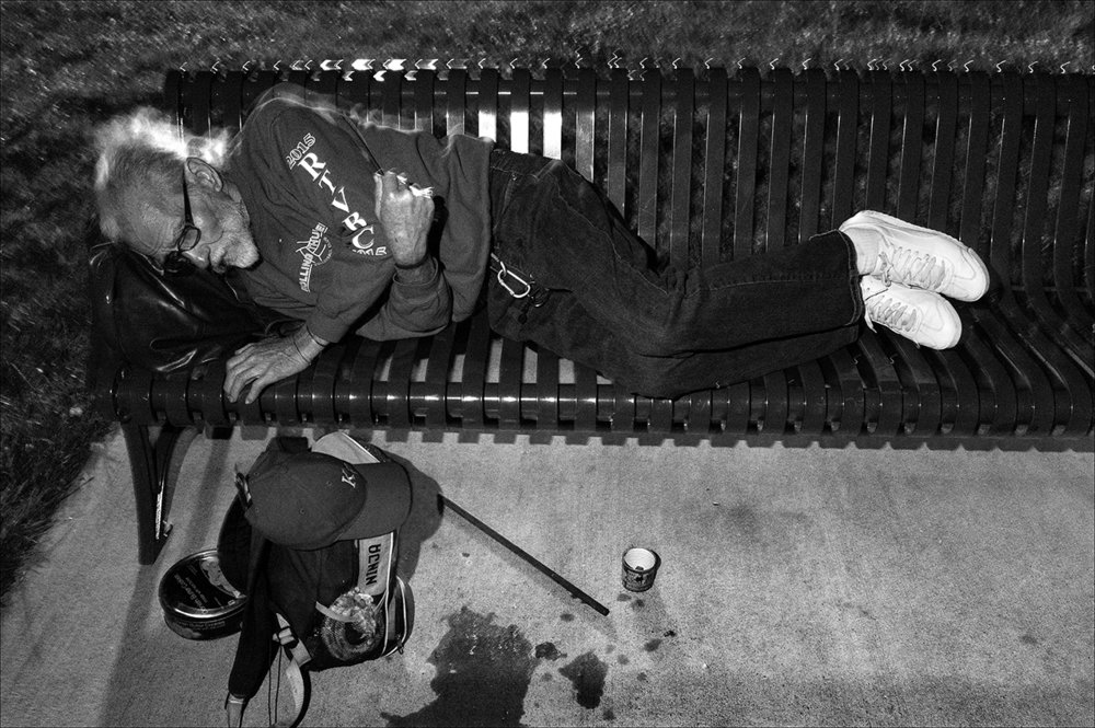 "May 2017:  Walter sleeps on a bench in Clat Adams Park after being evicted from the house in which he had been living. The bench is just wide enough for him. ""It was fairly comfortable 'cause I had my backpack with my clothes, my stuff in it.  I put it up against the arm of the bench I have to sleep sort of sitting up anyway. I have a breathing problem that makes it hard for me to lay flat."" He later moves to sleeping on downtown sidewalks."