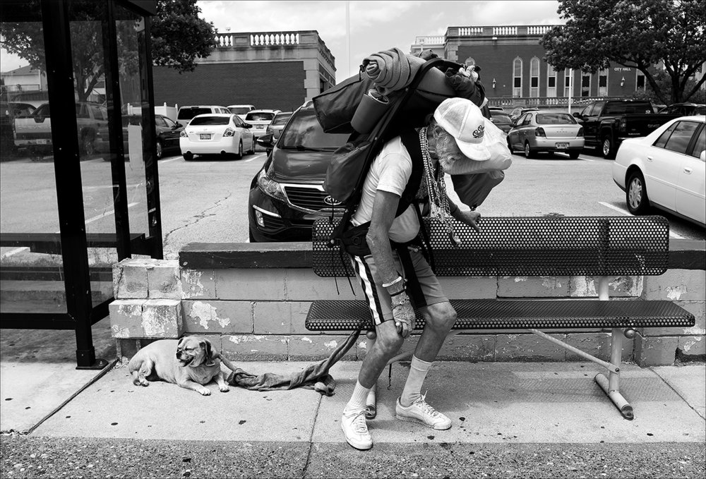 "May 2017:  Homeless for two days now, Walter balances himself under the weight of his backpacks as he sits on a bench to rest. He made a makeshift leash for his dog with shirtsleeves tied together. ""This is all I have left in the world. … Sandy died, then her dog died, then I had pneumonia. Now I'm homeless, but nobody will know any of this a hundred years from now."""