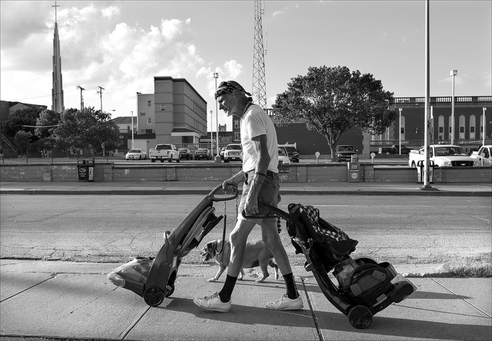 "June 2017:  Walter and his dog, Blondie, walk down a sidewalk with two vacuum machines Walter recovered from a nearby dumpster. He hopes to sell them. Blondie, like Walter, is homeless.  ""Blondie's a good dog. She's 14 years old.  She's like a 90-something-year-old person so she's kind of slow getting up.  She walks at a pretty good trot. She's a darn good dog, a little pug beagle. They call a puggie. I call her a puzzle. You don't never know what she's gonna act like sometimes she be stubborn as all get out. Other times she be just as loving as you'd want. She's a good dog, though.  One day while Walter was homeless, a passerby noticed Walter and Blondie resting near a convenience store and called 9-1-1 because of his concern for the dog. When the police arrived they told the man that if they confiscated the dog she would risk being euthanized. The man asked Walter if he would allow him to foster Blondie for a while. Walter agreed and after a few weeks Walter found a temporary place to stay and retrieved Blondie.  Blondie lives on food scraps Walter saves for her from the soup kitchen. ""Food stamps don't buy Gravy Train. … Blondie, she ain't worth two cents, but I wouldn't take $100 for her even though I could use the money real bad."""