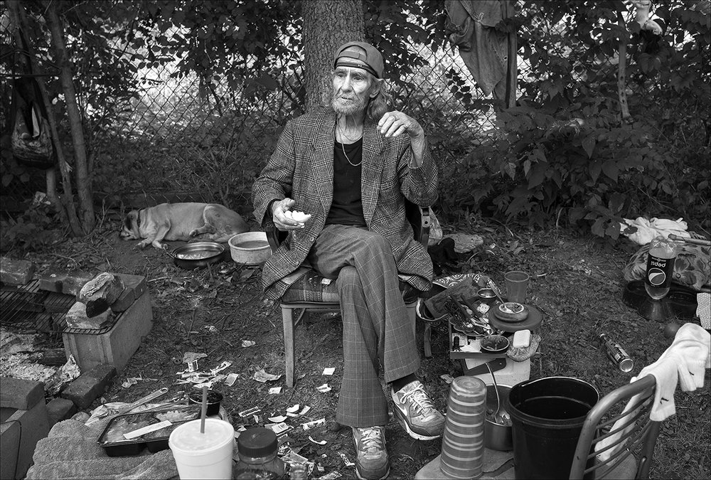 """A ugust 2017:  Walter relaxes in the backyard of the house he rented on Quincy's north side after eight weeks of homelessness. Walter says he's paying $350 a month rent and another $50 a month to use the washer and dryer his landlady left in the house. There's no heat or electricity because the landlady's son actually removed the utilities meter. Waiting for the meter to be replaced, Walter is living part-time in the yard, where he cooks on an open fire.  """"I've been living in the backyard for a month and a half making cowboy coffee, you know what that is, where you can stand a spoon up in it? I got a pretty good setup here in my backyard, I got me a barbecue pit that would hold at least a half of a cow, maybe the full damn cow. I built it myself out of cinder blocks, bricks and grates that a man gave me off a barbecue he had.  Walter did some work for a man who paid him with three lawn mowers, three barbecue grills, and three air conditioners, all of which Walter planned to repair and sell. Then, Walter says, people began stealing from him.  """"There was a Craftsman, self-propelled, damn good lawnmower. I just needed to put some rear wheels on it. And there was a 'green machine' … You know what I'm talking about when I say 'green machine'? Weed Eater brand. I went after my last lawnmower, I already had two here, I think. While I was going after the third one, someone come in, took the two I already had here, plus a weed eater that I paid $100 for. It makes me angry after buying something and having it come up missing a week later. I finally got a phone after six months without one and it came up missing too. They're in a pawn shop by now.""""  A few months later, Walter's backpack with all of his personal records is stolen. He must replace everything — his driver's license, Social Security card, his SNAP card.  It takes weeks to replace the identification cards he needs to reapply for his SNAP card."""