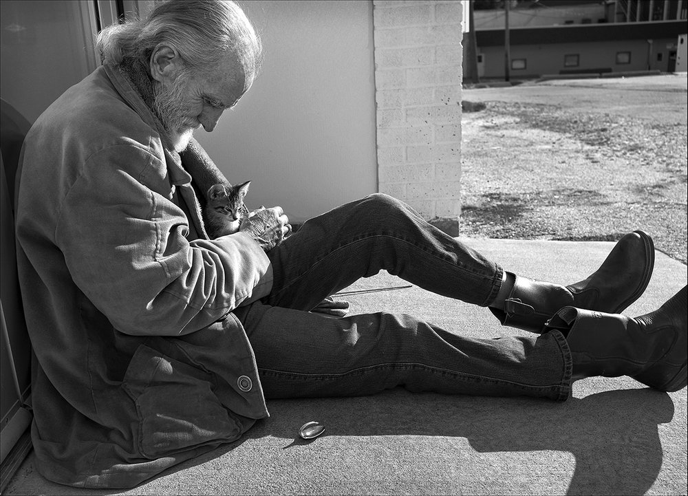 October 2017:  Walter waits in the warm sunlight with his new kitten outside the doors of the Horizons Soup Kitchen in Quincy. A few days later he found the kitten dead in his yard.