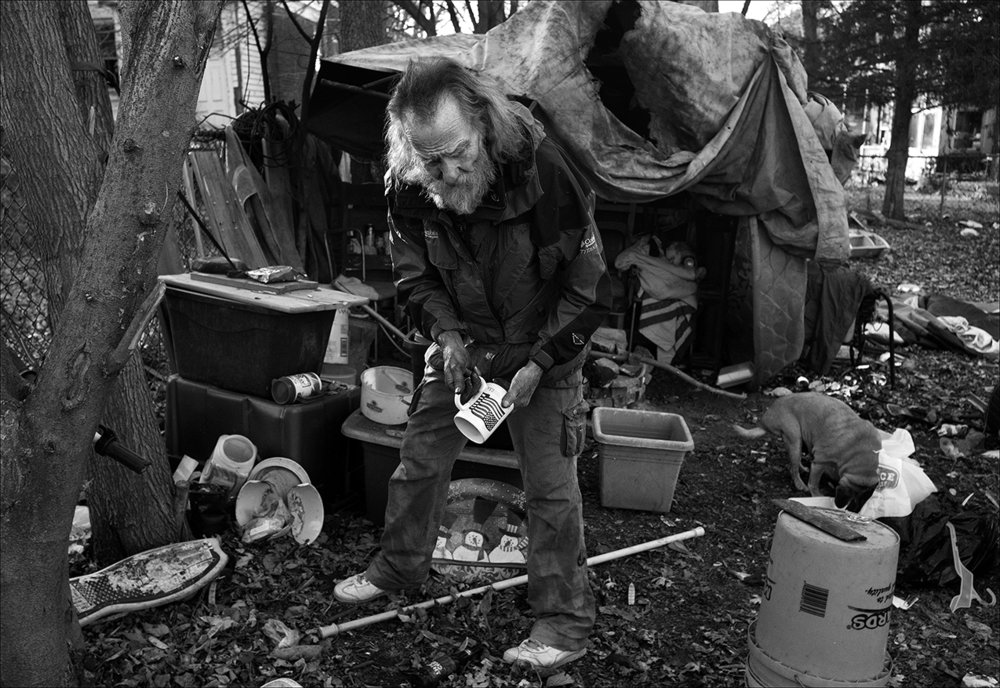"""December 2017:  On a cold December day, Walter organizes a living area in his homemade shelter made of mattresses, tarps and a plastic swimming pool. The utilities meter still has not been installed in the house he rented back in July. The house remains without heat and water pipes have frozen. Walter says the homeowner told him, on a handshake, she would do a rent-to-own agreement with him, but that the landlady's son is harassing him.  """"Well, I've been living in my back yard. At first, I was just around a fire pit sitting in a chair but since it's got cold and it's going into December it's getting cold out there. I get kind of smudgy (from the fire soot) but it helps out. The way you deal with the smoke is you sit down and let it go over your head. I can heat water over the fire pit and wash off, but it's not like being in a house with a shower and all that, and most people wouldn't know. The landlady's son jerked the meter out and evidently he messed up the meter box while he was taking it out because the power company will not turn it on with the meter box in the shape it's in. It's just got a small piece missing but that' rules and regulations that we have to go by if we wanna live and do well.  """"I couldn't get anybody to co-sign for me so I could buy a house with a regular mortgage so I had to rent-to-own which is risky, as far as I'm concerned, but rent-to-own is the only option I've got. I pay $350 plus bills for the house and also have a washer and dryer I could be using now with electricity, but I pay $50 a month on that so it makes it $400 plus bills for the whole thing. I like the house and the yard. It needs a little work on it but I know I'll do that. It takes time and a little material. But the location is the worst in Quincy. And there is a lot of thieving and drug-dealing and all that stuff going on right around me and in my yard. So it's really not a place that most people would want to live."""""""