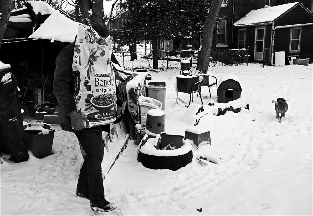 """December 2017:  Walter carries a bag of dog food, donated by a local good Samaritan, from his backyard shelter to the house he rents, which still has no electricity or heat. He says he must put the dog food in the refrigerator, which doesn't work, to keep mice and rats from getting into it. Now five months later, the utilities meter is still not replaced so Walter use his open fireplace to keep warm and cook meals from canned food the receives at local food pantries. Freezing weather takes its toll, however. Walter spends many evenings in fast-food restaurants to stay warm and a friend allows him to stop by and take a shower every couple of weeks.  """"I got the Good Lord on my side. In fact, I'm one of the richest bitches on earth, if you wanna put it that way. I really got no worries except what's in my mind that Lucifer put there. I just decided to live it day by day. Come what may and let the Good Lord take care of the assholes on this earth. I am still kicking, I will stay on this earth as long as the Good Lord says so. What that Man says come, I don't give a damn if you're the president of the United States, you come. That's my belief. If a man don't live by his beliefs he ain't much of a man."""