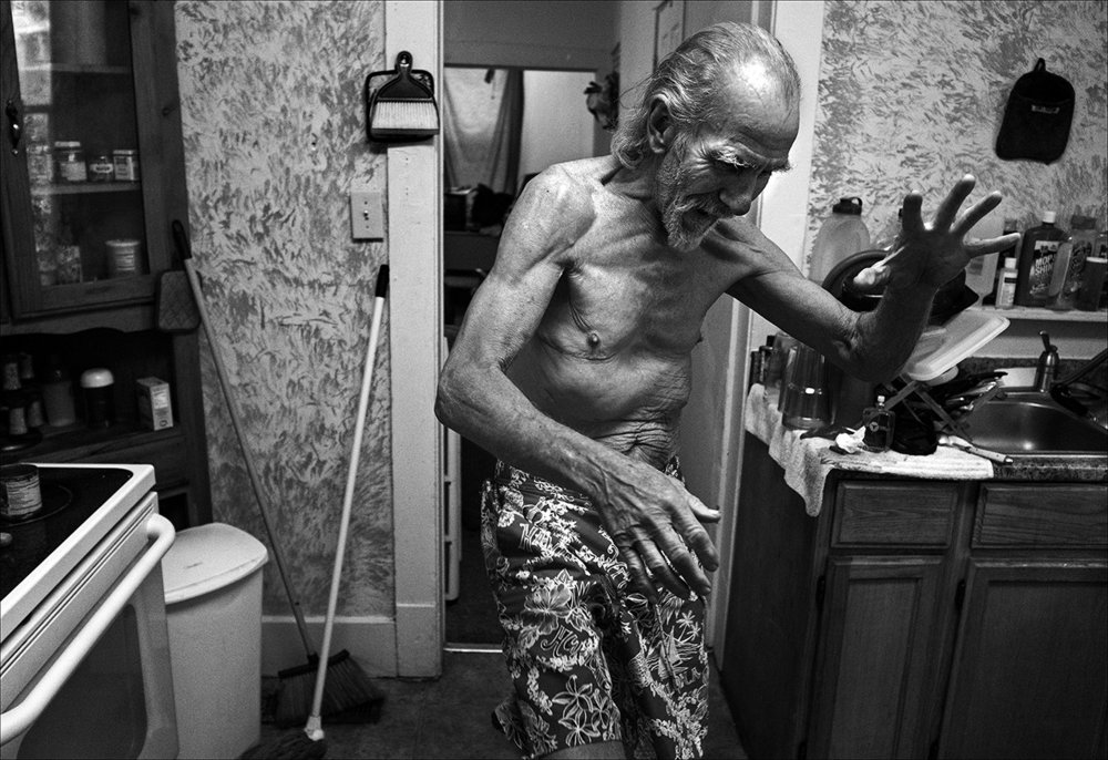 """April 2017:  Walter, in his kitchen, prepares to launch a """"karate kick"""" to demonstrate his physical prowess at age 72."""