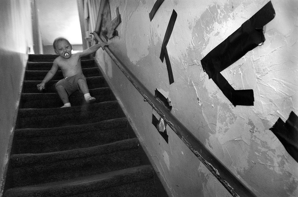 August 2017:  Carson, 3, makes his way down the staircase. The plaster patches and duct tape on the walls are the result of Wendy's daughter's boyfriend's attempt to cover several holes that have been there since before the Smiths moved in. Wendy and Chris say the first landlord said he would make the needed repairs but never did. They say when their current landlord purchased the house more than a year ago he said he would make the repairs to the walls. But a year later, no repairs.