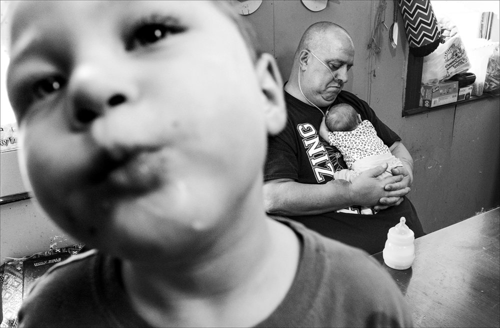 February 2018:  Chris cradles his new granddaughter, Madison Lou May, in his arms. Chris was told the cancer is spreading to other organs in his body and he has perhaps two or three months to live. Hospice arrangements have been made. Chris died within three weeks, on April 15, 2017 at age 57.