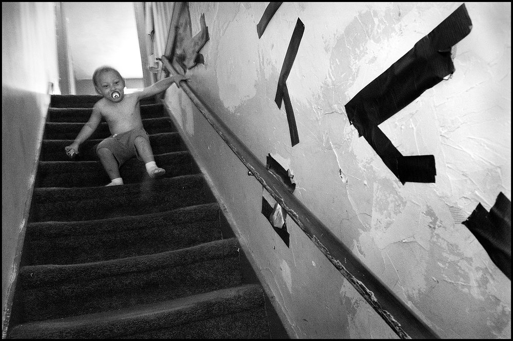 August 2017:  Carson, 3, makes his way down the staircase. The plaster patches and duct tape on the walls of this Quincy rental duplex are the result of Wendy's daughter's boyfriend's attempt to cover several holes that have been there since before the Smith's moved in. Wendy and Chris say the first landlord said he would make the needed repairs but never did. They say when their current landlord purchased the house more than a year ago he said he would make the repairs to the walls. But a year later, no repairs.