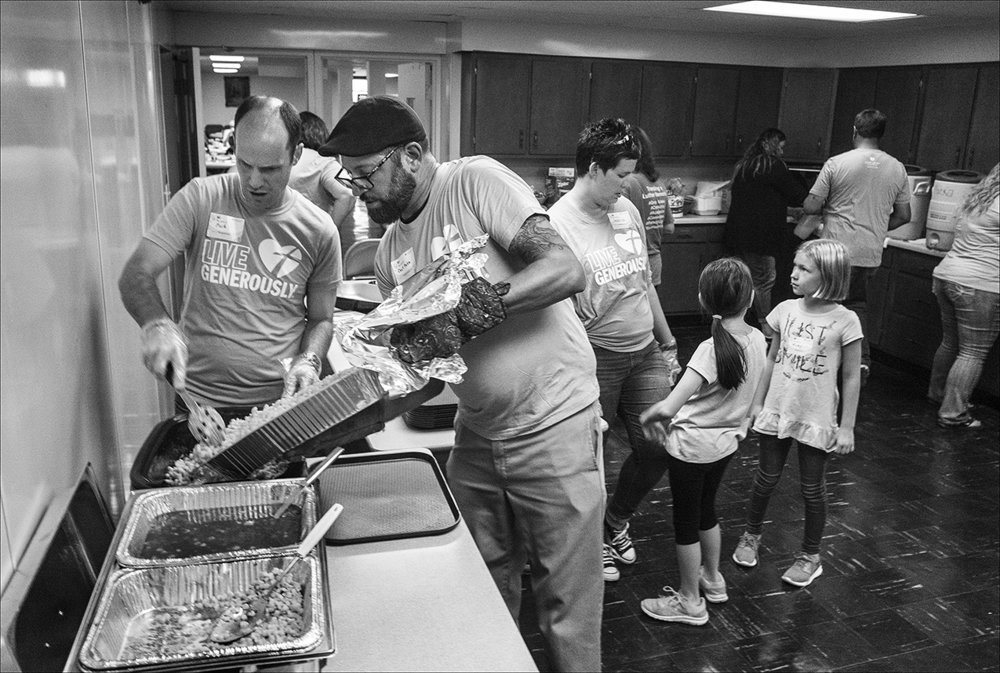 Quincy Chef Pete Maggliocco, center, loads up the pulled pork during a dinner party held for those who struggle making ends meet, Sunday, Sept. 23, 2018 at Luther Memorial Church in Quincy, Illinois.