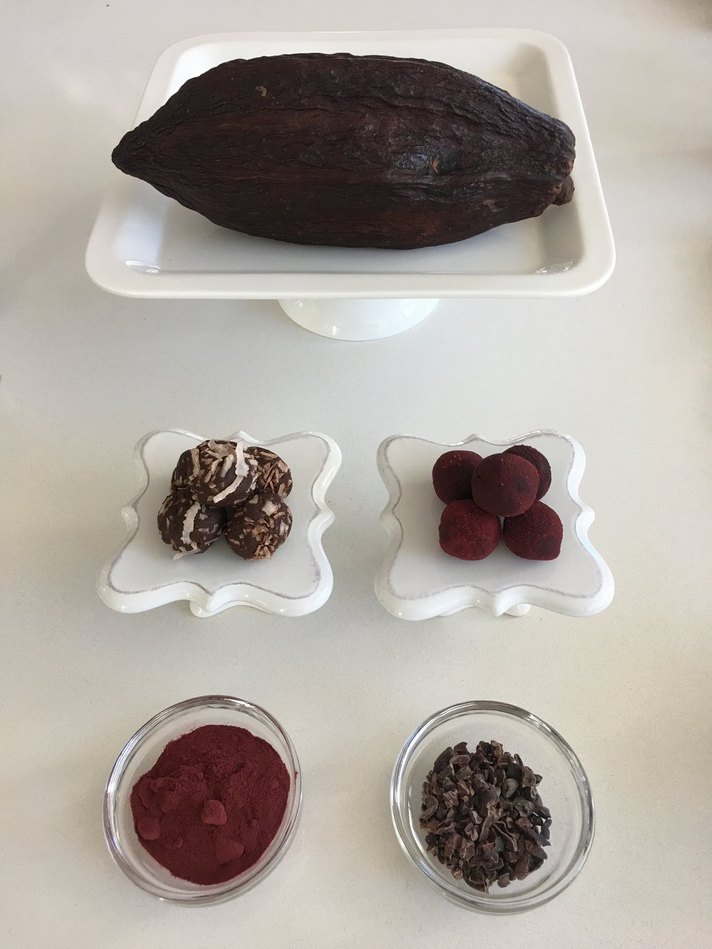 CACAO POD ( top ),Cacao Protein Bites rolled in shredded coconut and beet root powder ( middle ), Beet root powder, Raw cacao nibs ( bottom )