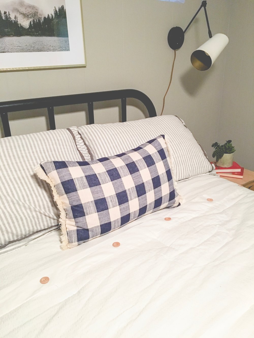 Our boring guest room gets a whole new modern cozy chic cabin look! Learn how to redecorate your guest room so it feels cozy and welcoming. A plaid lumbar pillow is the perfect finishing touch.