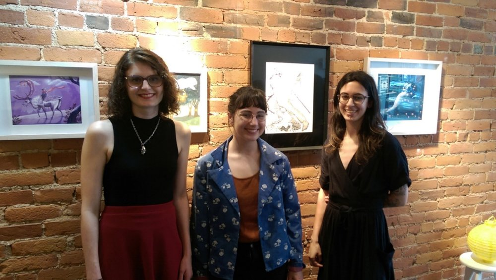 Artists Amy Titus, Madison Safer, and Natalie Kassirer stand in front of their work in the gallery.