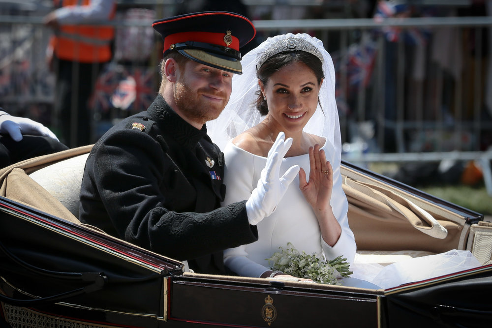 Prince Harry, Duke of Sussex and his wife Meghan Markle, Duchess of Sussex wave from the Ascot Landau Carriage during the procession after their wedding in Windsor Castle.