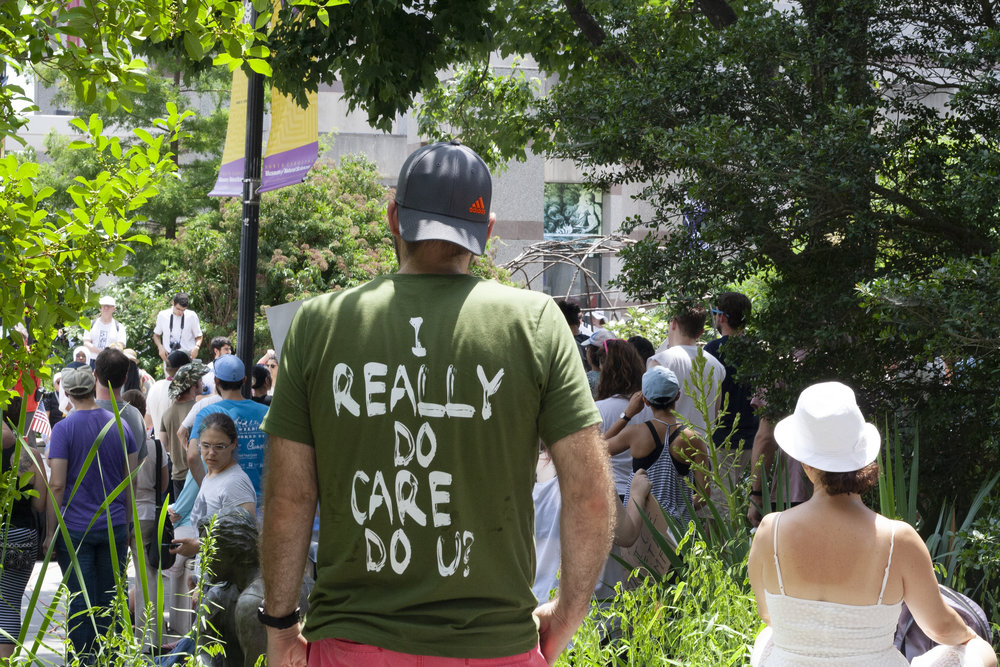 "A man, wearing a shirt referencing Melania Trump's infamous jacket stating ""I really don't care, do you?"" while she boarded an Air Force plane to visit a Texas detention center, listens to the speakers."
