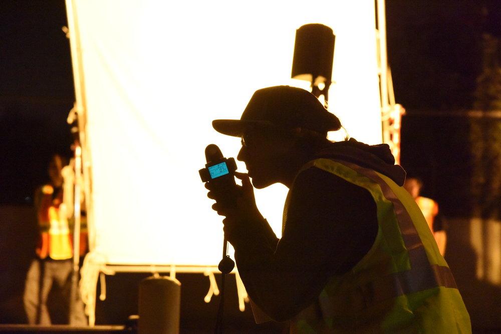 DP  Michal Wronski  measures the light for a scene.