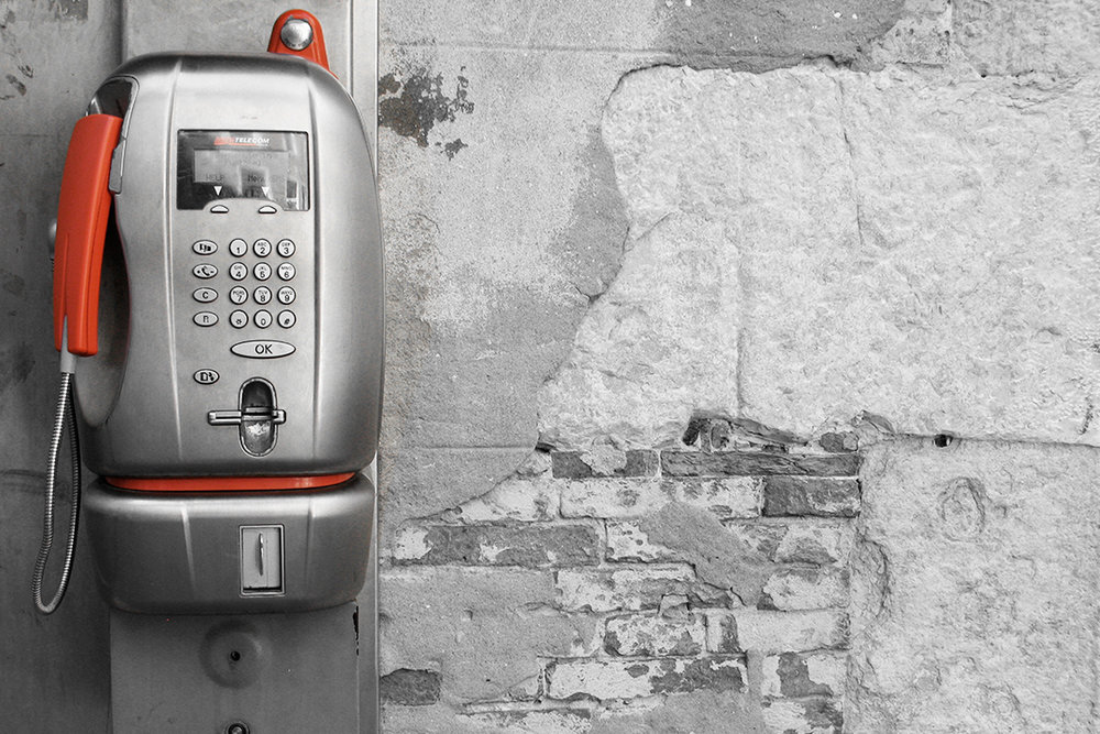Red pay phone on decaying brick wall suggests cultural layers of communication