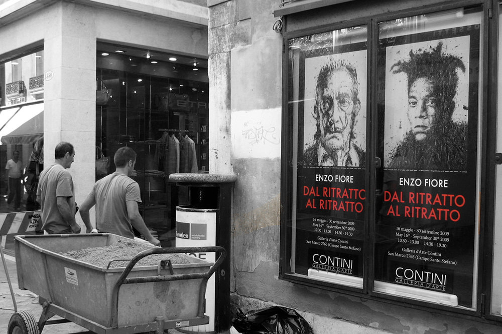Streetscape with construction workers near ads for an Enzo Fiore exhibition and upmarket shopfronts, suggesting cultural contrasts