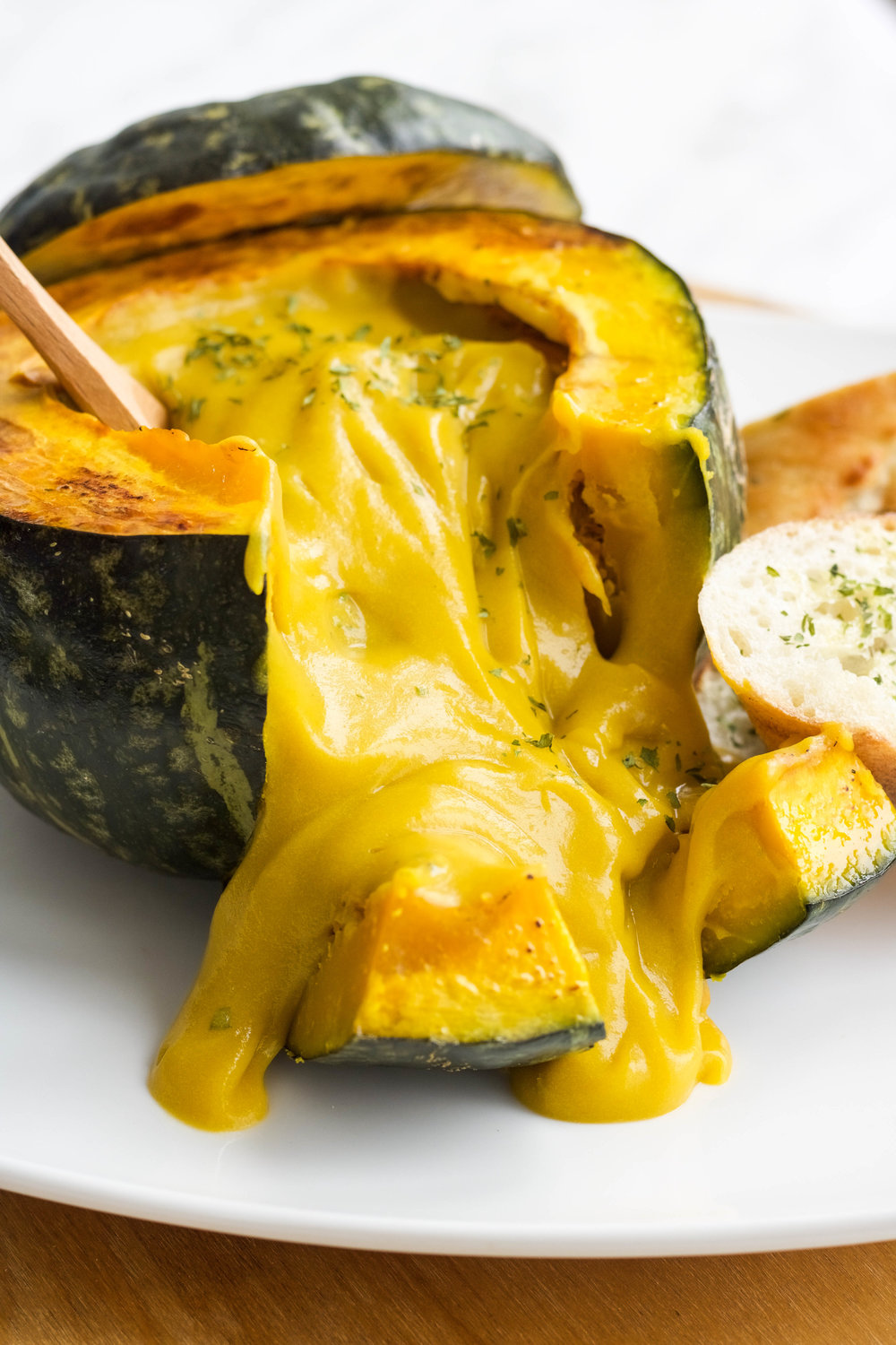Ingredients:  1 small onion  1 med potato (around 150g)  1/2 carrot (approx 40g)  1.5 lbs kabocha squash*  2 c + 1/4c veg stock  1 c soy milk**  Optional: Additional squashed to make kabocha bowls  Method:  1. If making kabocha bowls, pre-heat oven to 350  2. Cut upper half of the squash and discard the seeds  3. Place on a baking tray and place in oven for 30 minutes  4. Chop up the onion, carrot, potato and kabocha into small pieces  5. Sautee the onions lightly  6. Add in the carrots, potatoes and kabocha and let it sautee for a few minutes  7. Add in the veggie broth and let it come to a boil and then reduce to a simmer for approx 40 minutes or until you can mash the potatoes and kabocha with a fork  8. Remove from heat and let it cool  9. Once slightly cooled, transfer to a blender and add soy milk  10. Pour it into the kabocha bowls and serve with toasted garlic baguettes!      Notes:  1. Buttercup squash may be substituted   2. Add more for a thinner consistency!