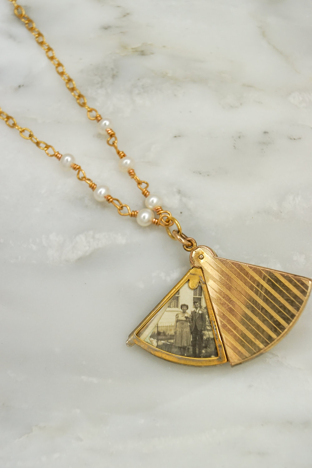 Gold antique locket on pearl necklace.