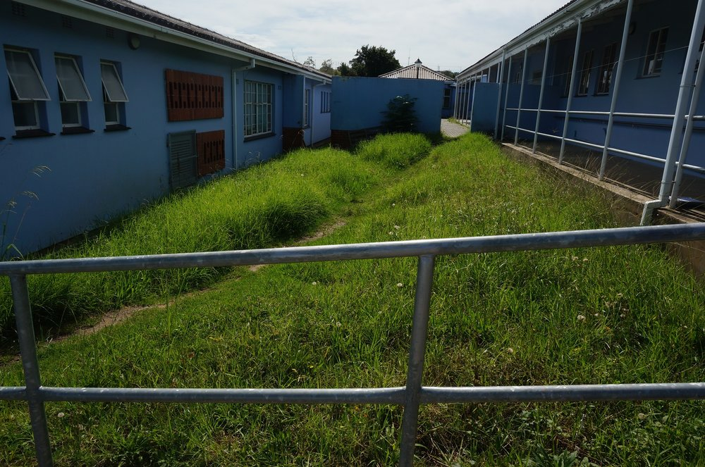 The school has some paved, covered hallways but also a number of uneven pathways. Credit: UN-Habitat