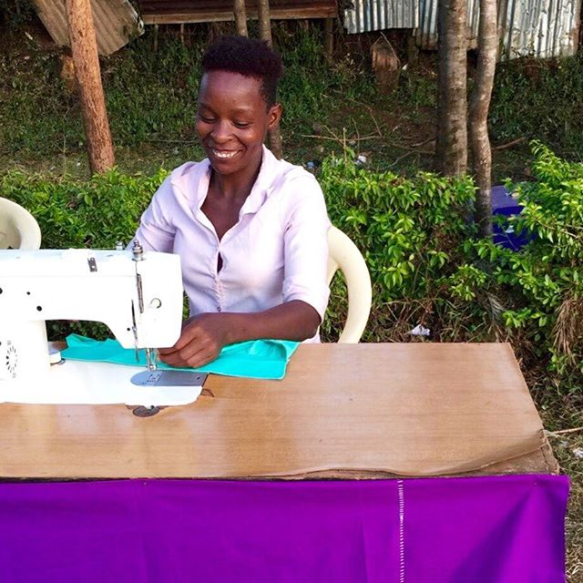 A seamstress works outside to sew uniforms for three of our new students at a Kenyan National School.