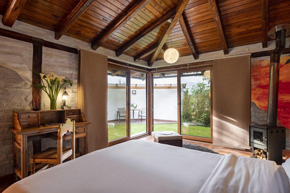 atardecer volcánico - Habitación Romántica #52 - Máx. 2 personas1 cama queen, chimenea y sala.Calefacción en el piso. Terraza privada con 1 mesa y 2 sillas.Vista al Volcán Tungurahua y al jardín.
