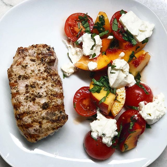 Perfect summer dinner: Grilled pork with a salad of tomatoes, peaches, basil and luscious dollops of burrata.  #cleaneating #healthyfood #instafood #food52 #glutenfree #eeeats #purewow #healthcoach #burrata #summer