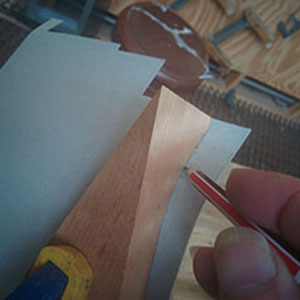 9. A piece of cardboard is clamped between the 2 sections of the trimming mould and the shape is traced.