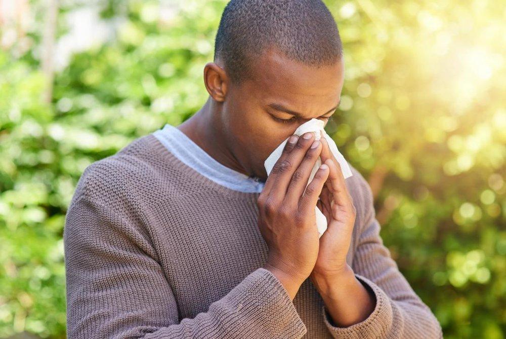 man sneezing allergies