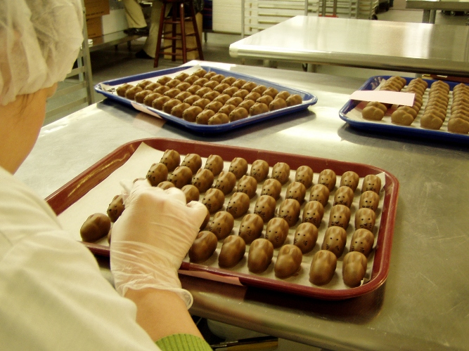 Moonstruck employee hand painting Easter truffles