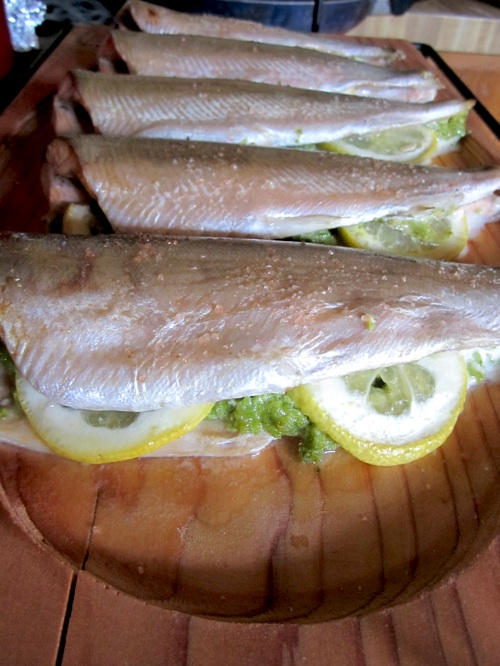 Kokanee trout stuffed with lemon and pesto and roasted on cedar.