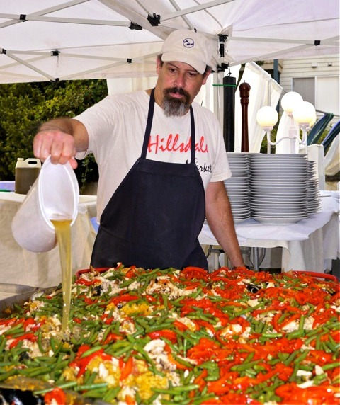 Chef Greg Higgins cooking up paella for 300 people at last year's Hillsdale Paella Party