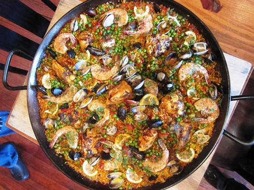 Save the best for last. The last recipe that we tested for the book was this paella. My feet are on the right, John's are on the left and we're about to dig in with the Toro staff...