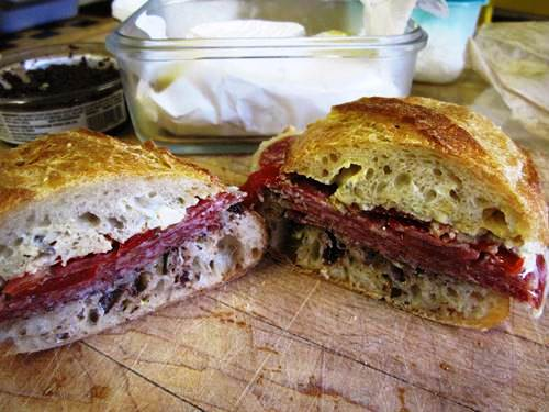 Baguette sandwich with Freybe salame, tapenade and pickled peppers.
